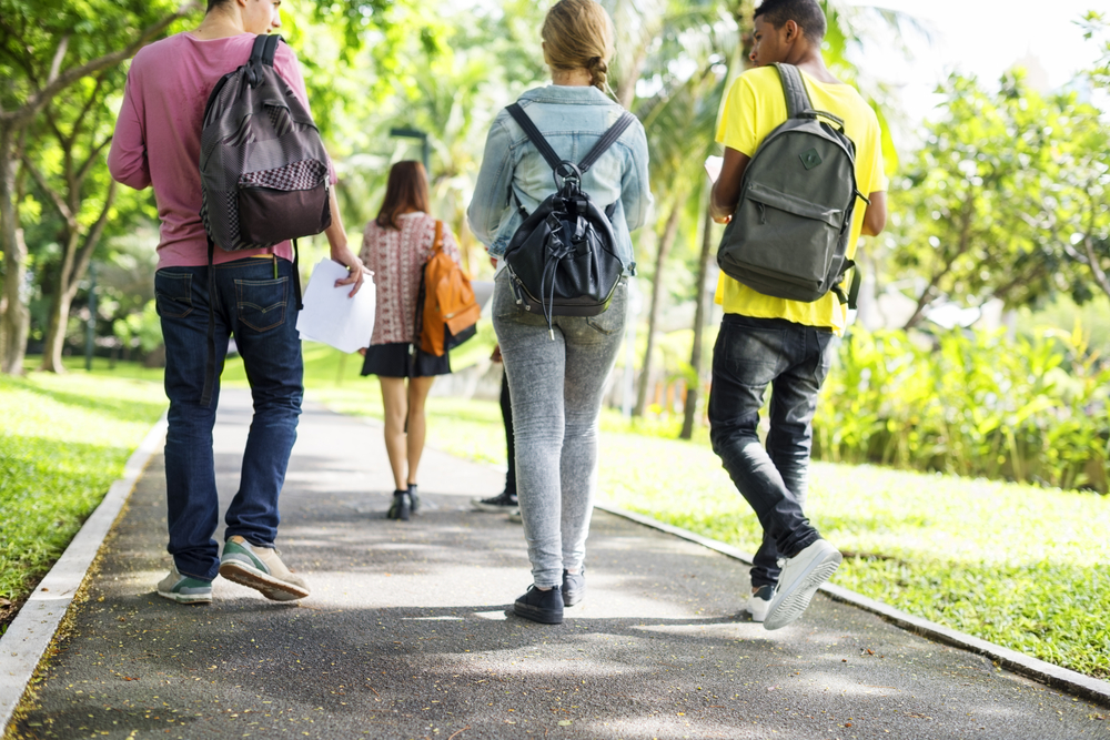 Students with backpacks walking outdoors