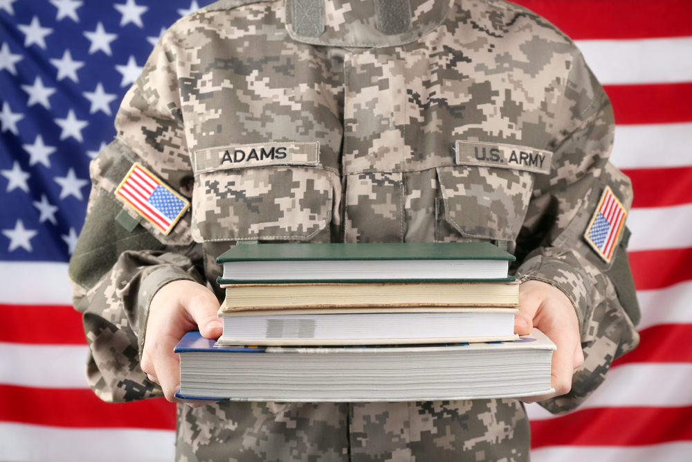 Female soldier holding books, with USA flag on background