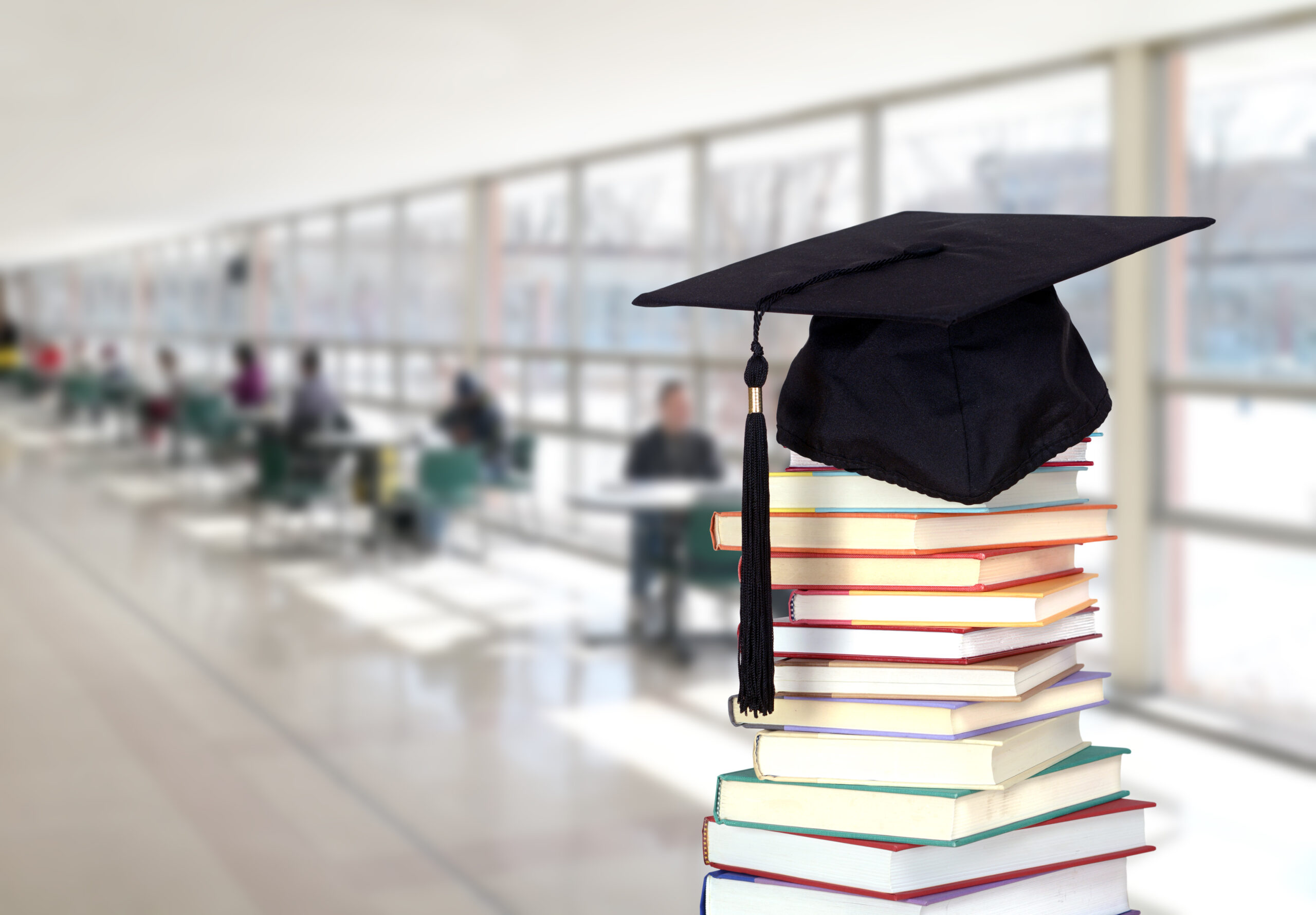 Stack of books with college graduation cap on top of it