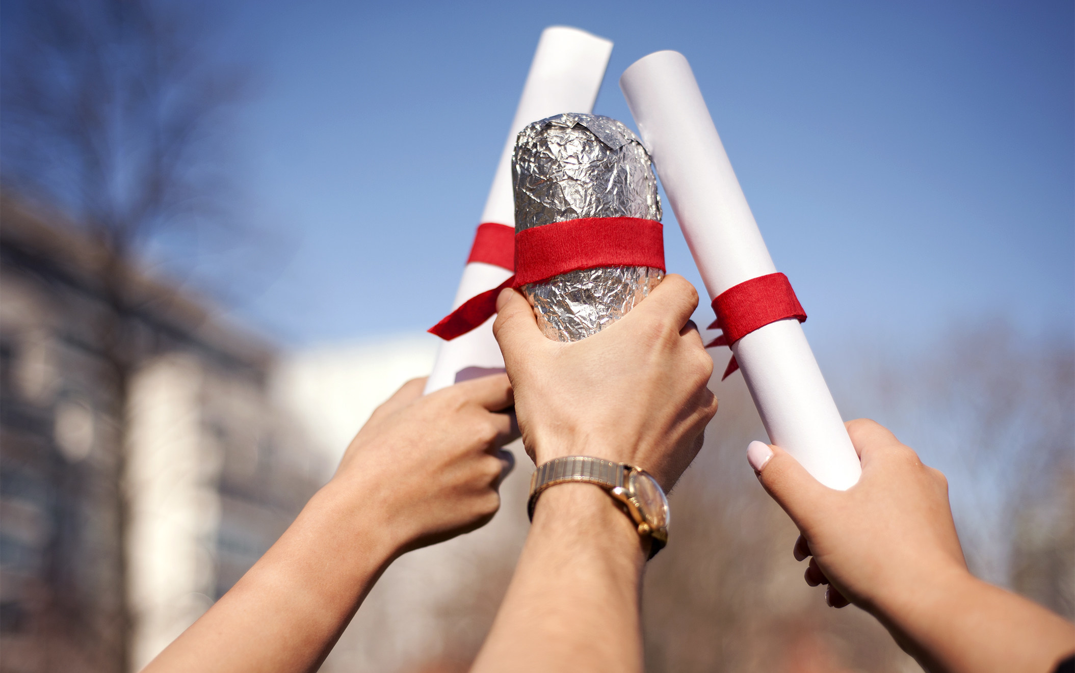Photo of hands holding up diplomas and a Chipotle burrito