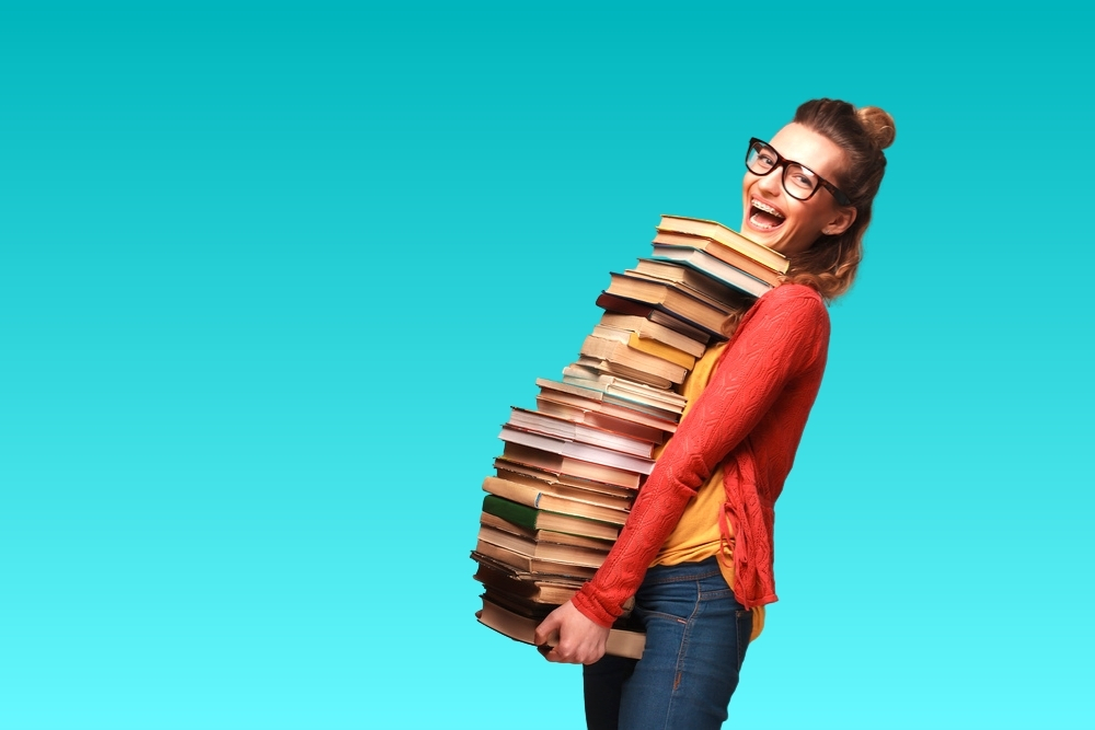 Photo of a student carrying a huge stack of college textbooks