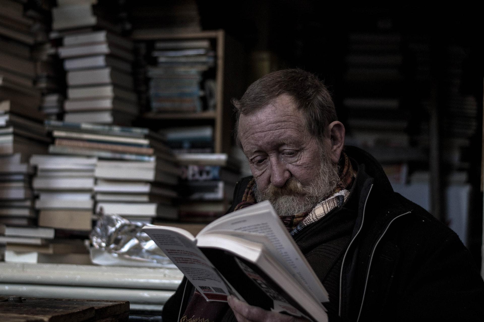 An elderly man reading a book.