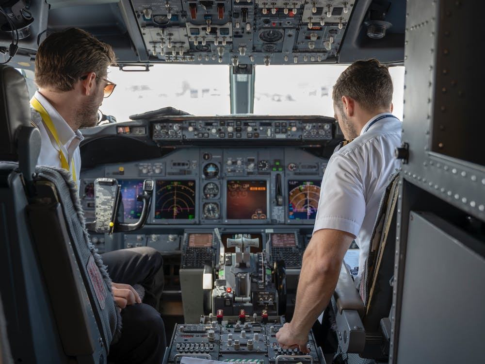 Two pilots sitting in the cockpit of an airplane