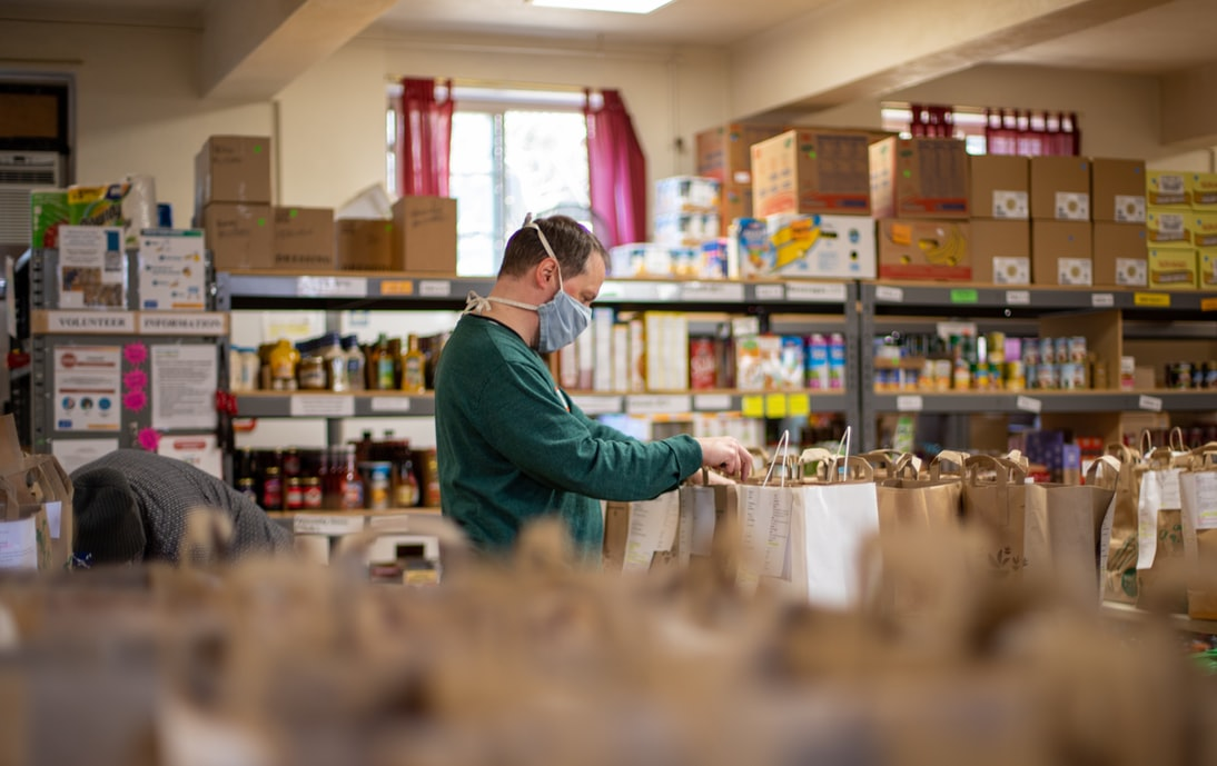 A man working in a food pantry during COVID