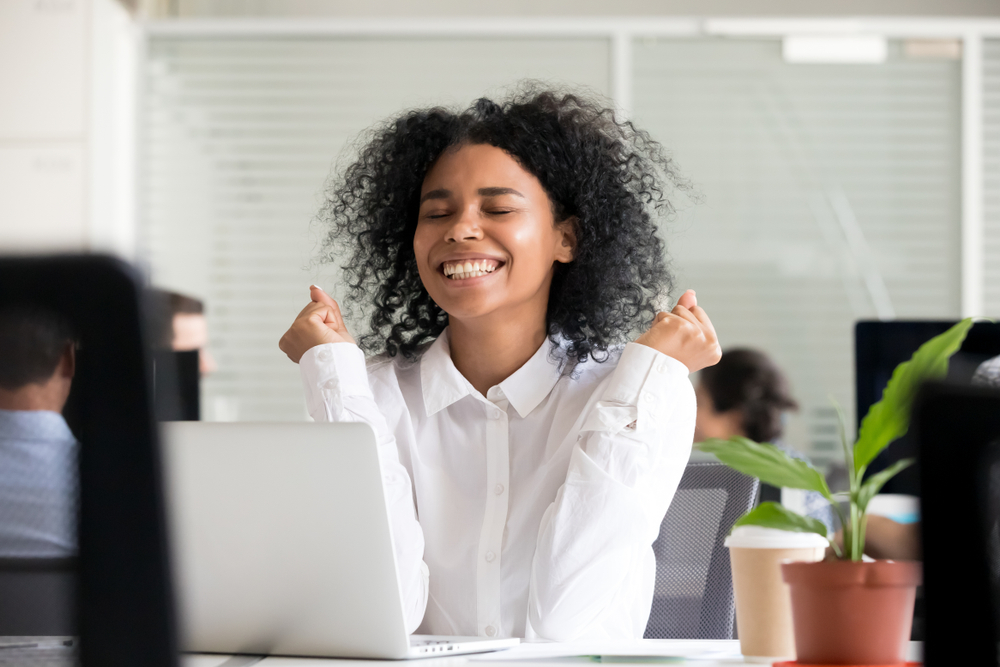 Excited office worker receives good news on her laptop