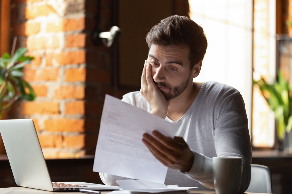 Confused, frustrated young man reading a letter