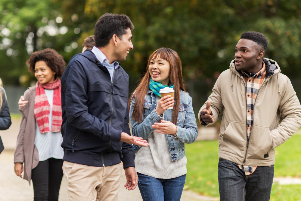 Students talk to each other while walking on campus
