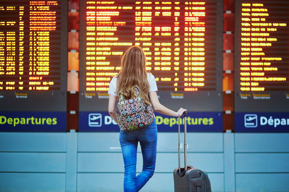 A young tourist girl in airport looking at the flight information board