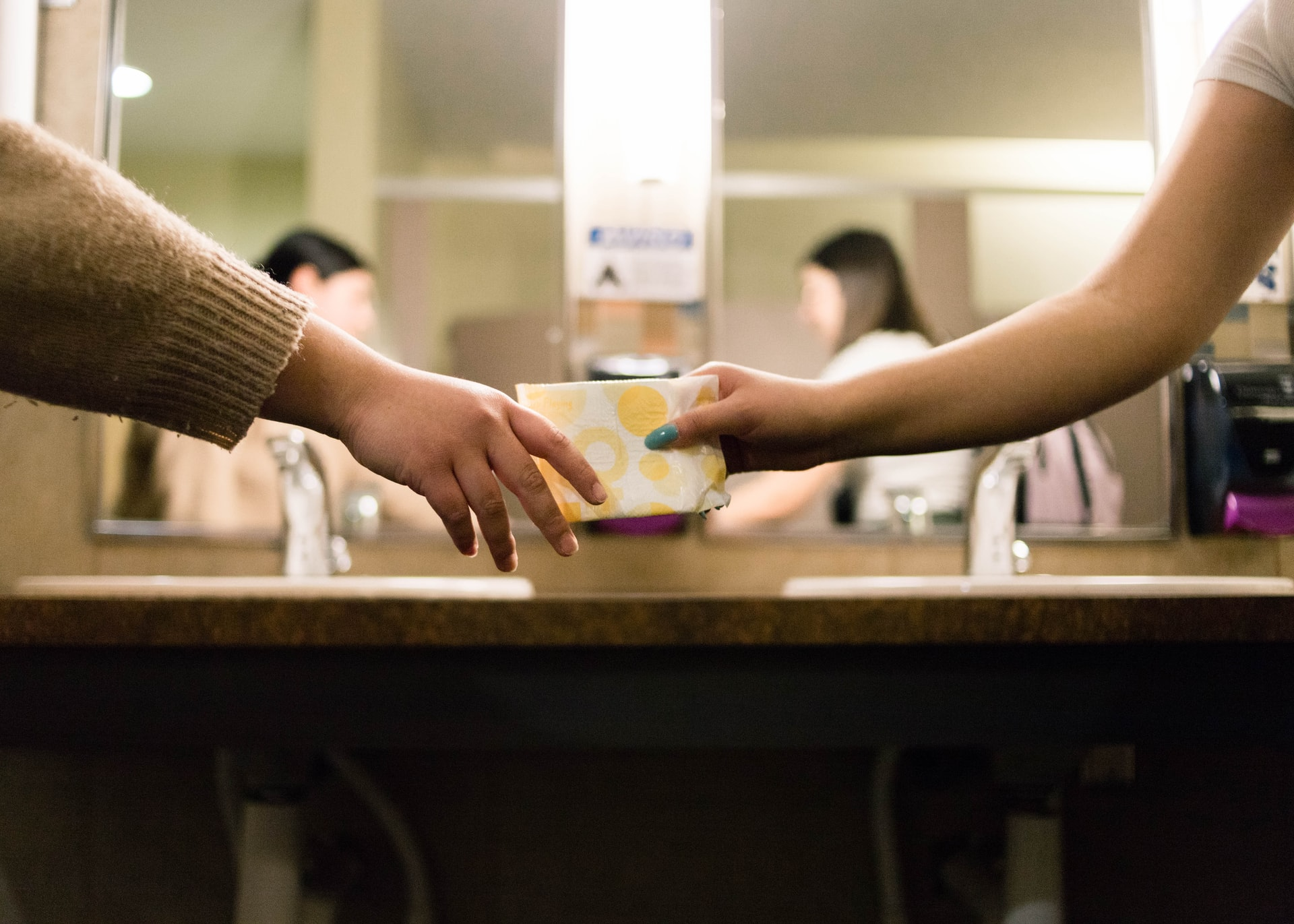 two girls sharing a menstrual pad in a bathroom